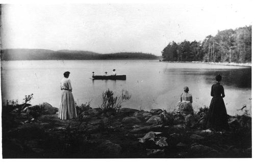 Women on West Hill shore watching men in boat